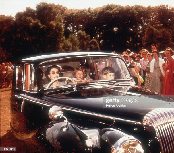 Queen Elizabeth II driving a Daimler saloon car with Prince Charles and Princess Anne as passengers circa 1957