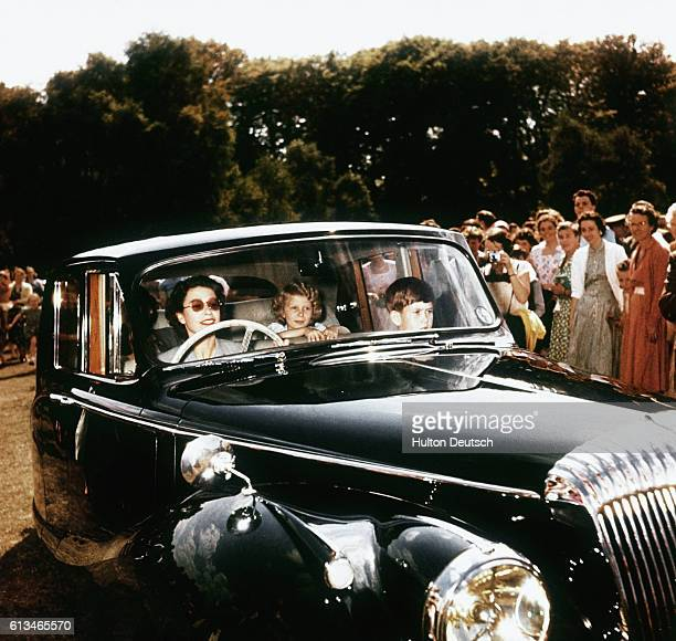 Queen Elizabeth II driving her children Prince Charles and Princess Anne at Windsor watched by a group of onlookers 1957