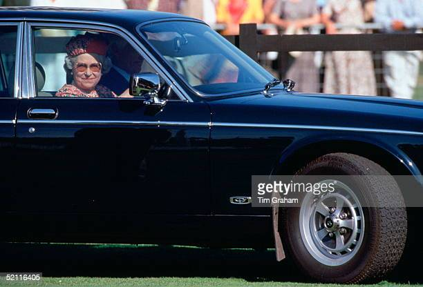 Queen Elizabeth II Driving Herself In Her Daimler Jaguar Car As She Arrives To Watch Polo At Smiths Lawn, Windsor.