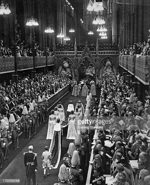 Queen Elizabeth II escorted by her maids of honour walks slowly towards the nave of Westminster Abbey during her Coronation 2nd June 1953 Behind the...