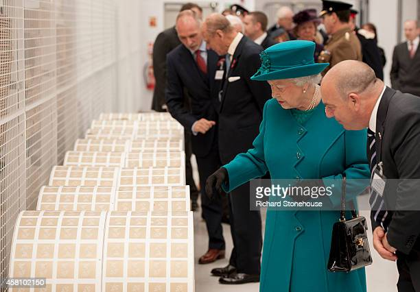 Queen Elizabeth II examines large rolls of stamps during an official visit to International Security Printers to view their work on specialist...