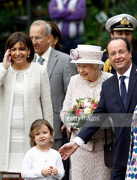 Queen Elizabeth II flanked by Anne Hidalgo Mayor of Paris and President of France Francois Hollande visits Paris Flower Market during a ceremony for...