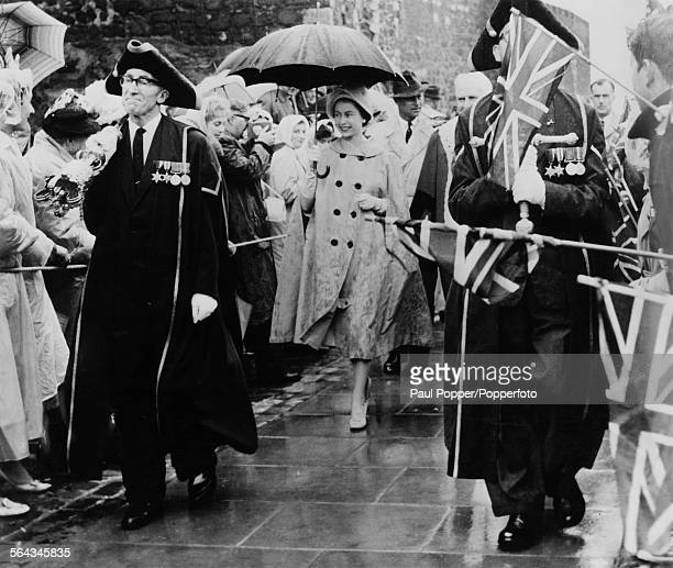 Queen Elizabeth II followed by Prince Philip arrive at Carrickfergus harbour preceded by a macebearer and a swordbearer during a twoday official...