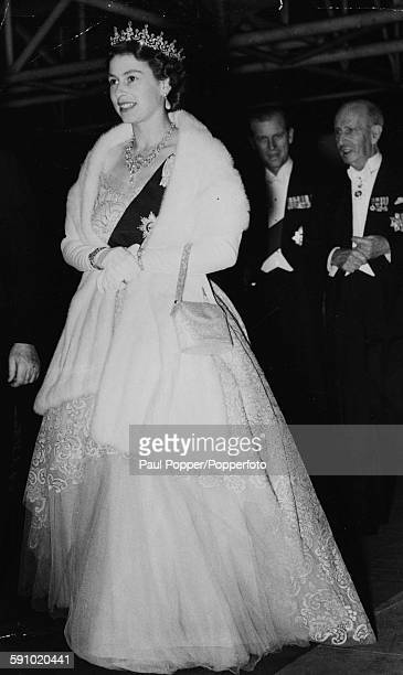 Queen Elizabeth II followed by Prince Philip Duke of Edinburgh wears a fur shawl crown and diamond necklace as she attends a concert at the Festival...