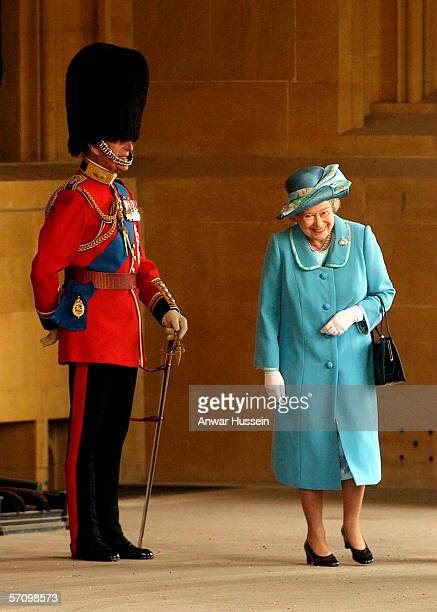 Queen Elizabeth II gets a fit of the giggles as she walks past her husband Prince Philip the Duke of Edinburgh who is standing to attention in his...