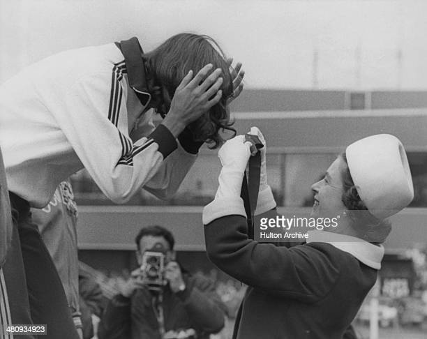 Queen Elizabeth II gets the ribbon entangled in the hair of Debbie Brill of Canada as she presents her with the gold medal for the High Jump at...
