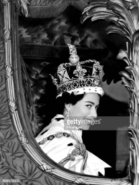 Queen Elizabeth II gives a wide smile for the crowd from her carriage as she leaves Westminster Abbey London after her Coronation