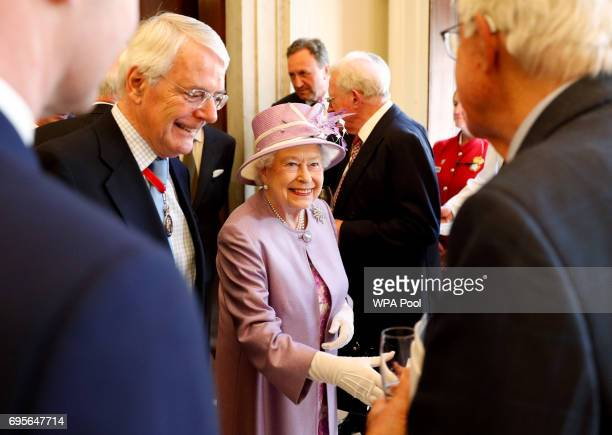 Queen Elizabeth II greets guests including former prime minister John Major at a reception after an Evensong service in celebration of the centenary...