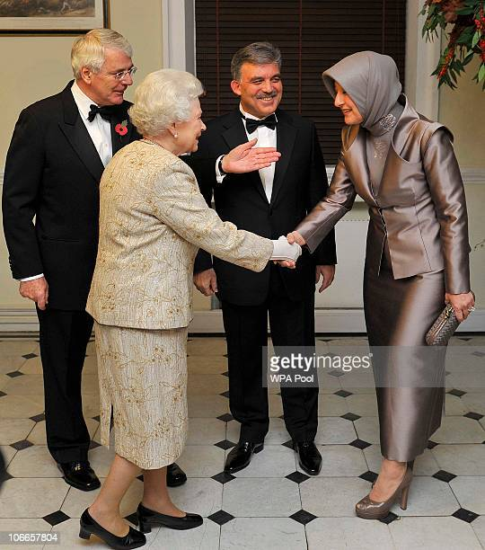 Queen Elizabeth II greets Hayrunnisa Gul the wife of the President of Turkey as Abdullah Gul and former British Prime Minister John Major looks on...