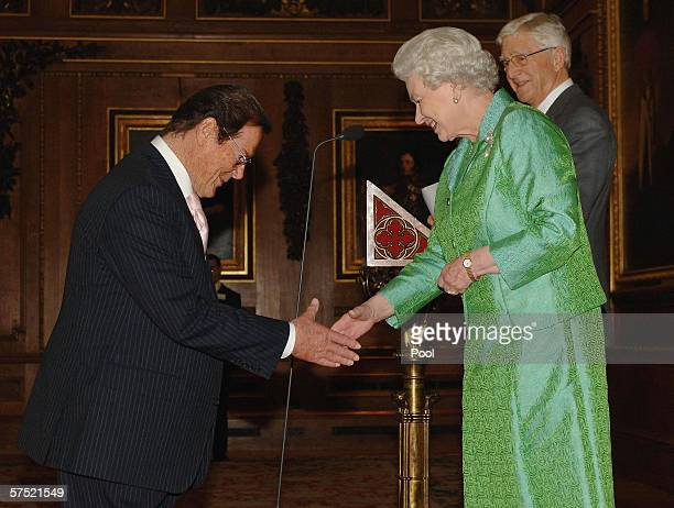 Queen Elizabeth II greets Help The Aged Living Legend award winner actor Sir Roger Moore as compere TV presenter Michael Parkinson looks on at a...