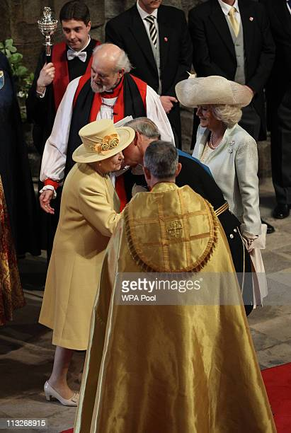 Queen Elizabeth II greets her son Prince Charles Prince of Wales as his wife Camilla Duchess of Cornwall and John Hall Dean of Westminster look on as...