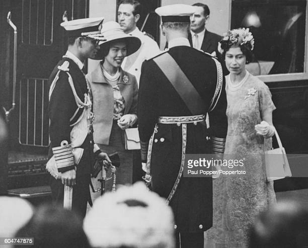 Queen Elizabeth II greets King Bhumibol Adulyadej of Thailand as Queen Sirikit and Prince Philip look on at Victoria Station in London at the start...