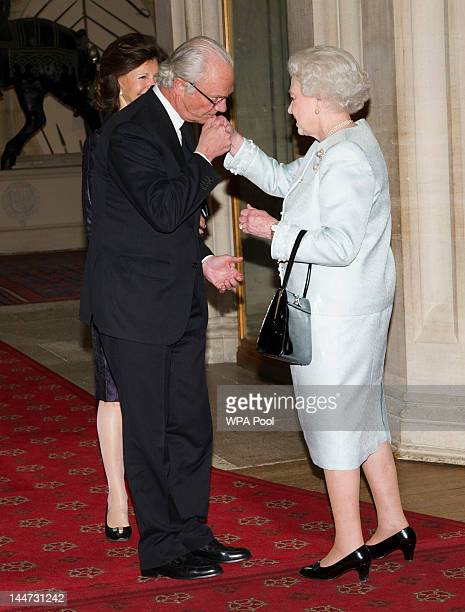 Queen Elizabeth II greets King Carl XVI Gustaf of Sweden and Queen Silvia of Sweden as they arrive at a lunch for Sovereign Monarch's held in honour...