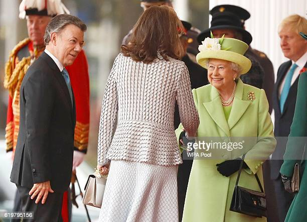 Queen Elizabeth II greets Maria Clemencia de Santos as her husband Colombia's President Juan Manuel Santos looks on at a ceremonial welcome for...