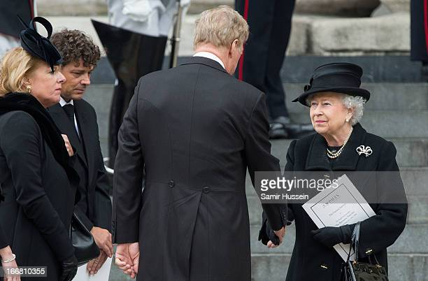 Queen Elizabeth II greets Mark Thatcher as Carol Thatcher looks on following the ceremonial funeral service of former British Prime Minister Margaret...