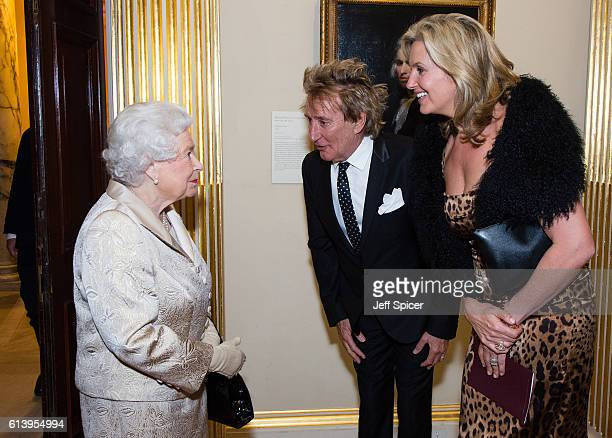 Queen Elizabeth II greets Sir Rod Stewart and wife Penny Lancaster after he was awarded a knighthood in recognition of his services to music and...