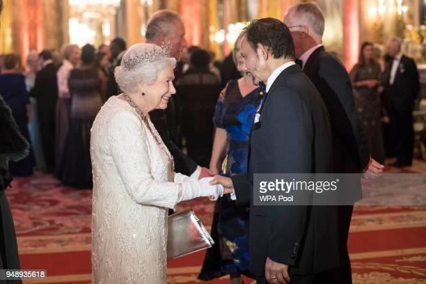 Queen Elizabeth II greets Sultan of Brunei Hassanal Bolkiah in the Blue Drawing Room in the Blue Drawing Room at The Queen's Dinner during the...