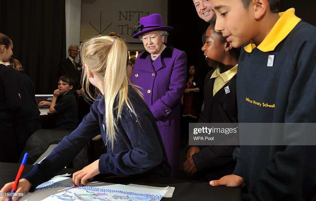 Queen Elizabeth II grimaces after a 10-year-old Tabby Kent (L) recalled the bad weather at the Thames Diamond Jubilee Pageant during a visit to the British Film Institute on October 25, 2012 on the Southbank in London, England.