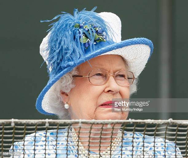 Queen Elizabeth II grimaces whilst watching the racing from the balcony of the Royal Box as she attends Derby Day during the Investec Derby Festival...