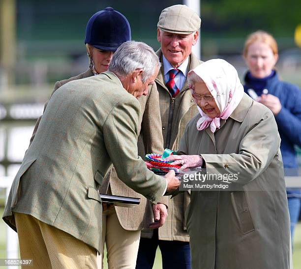 Queen Elizabeth II hands her stud groom Terry Pendry her rosettes after her horse Barbers Shop won the Tattersalls Ror Thoroughbred Ridden Show Horse...
