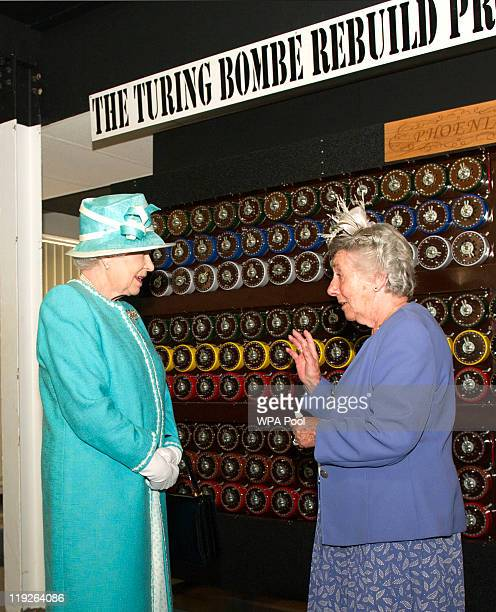 Queen Elizabeth II has a machine explained to her by wartime operator Jane Valentine during a visit to Bletchley Park on July 15 2011 in Milton...