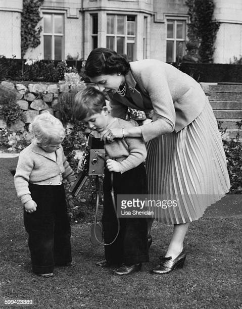 Queen Elizabeth II helps her son Prince Charles to take a picture of his sister Princess Anne Balmoral Scotland 1952