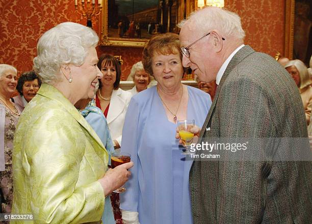 Queen Elizabeth II holding a glass of her favourite drink meets Allan Garrioch and his wife Helen at an 80th birthday lunch at home at Buckingham...