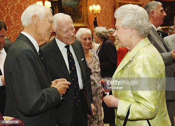 Queen Elizabeth II holding her favourite drink meets identical twins Keith and Jack Hurst at an 80th birthday lunch held by The Queen at Buckingham...