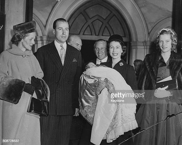 Queen Elizabeth II holding the baby after the christening of the son of Lord Porchester and Lady Porchester at St Paul's Knightsbridge London...