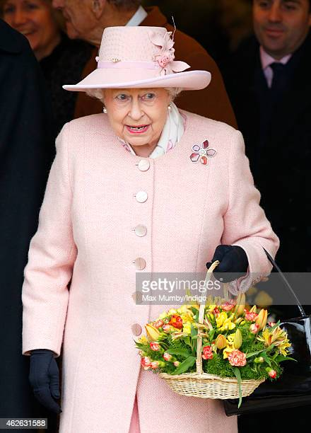 Queen Elizabeth II holds a basket of flowers as leaves leaves West Newton village hall after attending Sunday service at the church of St Peter and...