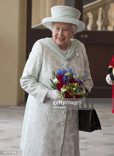 Queen Elizabeth II holds a bouquet of flowers as she arrives at Buckingham Palace at the end of a carriage procession following a national service of...