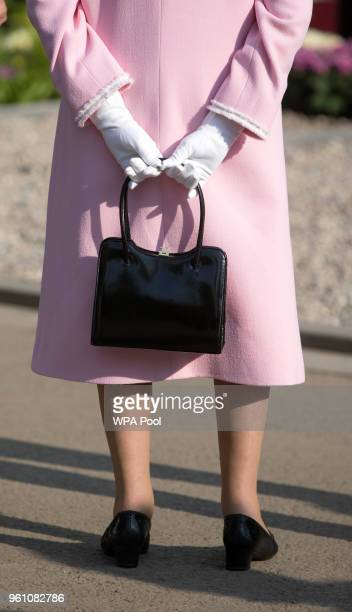 Queen Elizabeth II holds her bag behind her as she views a garden at the Chelsea Flower Show 2018 on May 21 2018 in London England