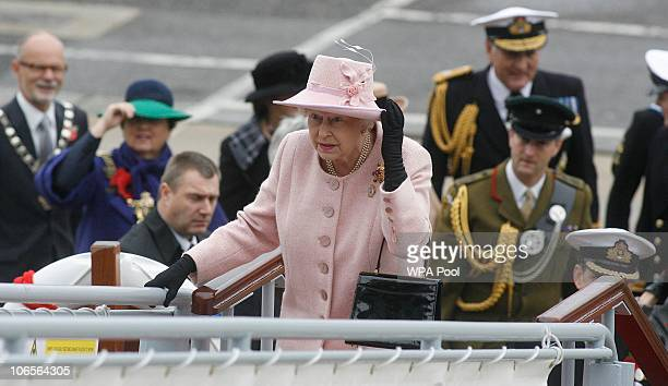 Queen Elizabeth II holds her hat as she boards HMS Ark Royal Queen Elizabeth II boarded the Ark Royal on November 5 2010 in Portsmouth United Kingdom...