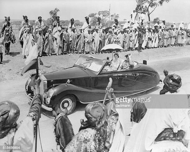 Queen Elizabeth II holds her own umbrella as she rides in an open Rolls Royce between rows of colorfully-garbed tribesmen at Kaduna, in Northern...