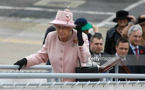 Queen Elizabeth II holds hert hat as she boards HMS Ark Royal on November 5 2010 in Portsmouth United Kingdom Queen Elizabeth II boarded the Ark...