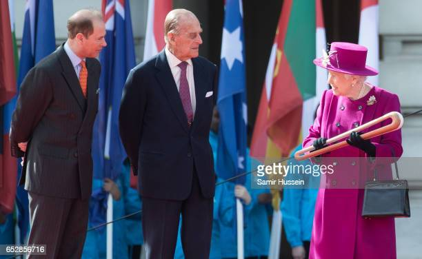 Queen Elizabeth II holds the Commonwealth baton as Prince Philip Duke of Edinburgh and Prince Edward Earl of Wessex attend the launch of The Queen's...