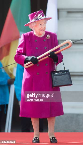 Queen Elizabeth II holds the Commonwealth baton during the launch of The Queen's Baton Relay for the XXI Commonwealth Games being held on the Gold...
