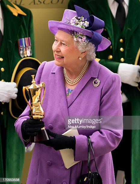 Queen Elizabeth II holds the Gold Cup after her horse Estimate won the feature race on Ladies Day of Royal Ascot at Ascot Racecourse on June 20 2013...
