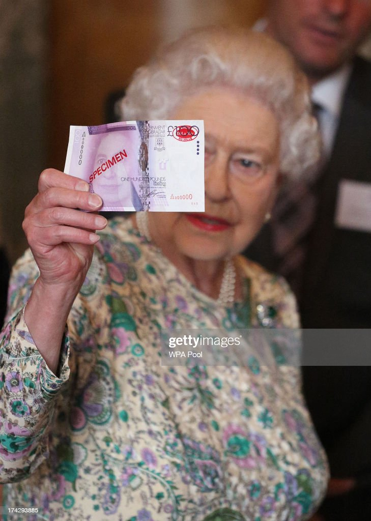 Queen Elizabeth II holds up a mock 100 pound note demonstrating a new sercurity strip at a reception for the Winners of the Queens Award for Enterprise 2013 at Buckingham Palace in London. Tuesday July 23, 2013.