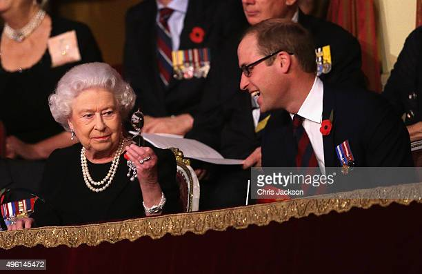 Queen Elizabeth II holds up her glasses after joking with Prince William Duke of Cambridge in the Royal Box at the Royal Albert Hall during the...
