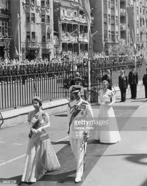 Queen Elizabeth II in a lace gown and Prince Philip Duke of Edinburgh wearing a white naval uniform arriving for the opening of parliament in New...