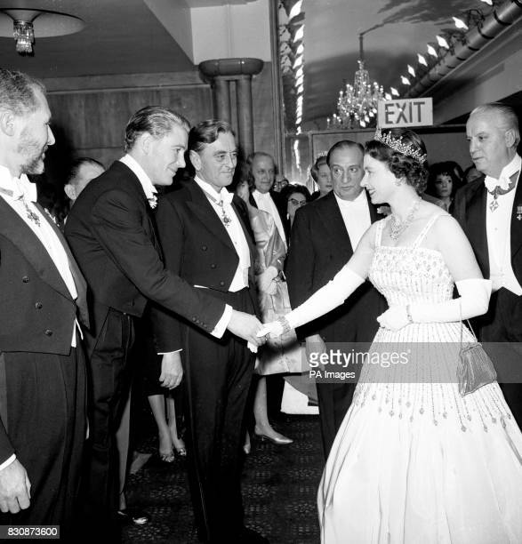 Queen Elizabeth II, in a white silk faille gown, shakes hands with Peter O'Toole when she meets him and other personalities before the world charity...
