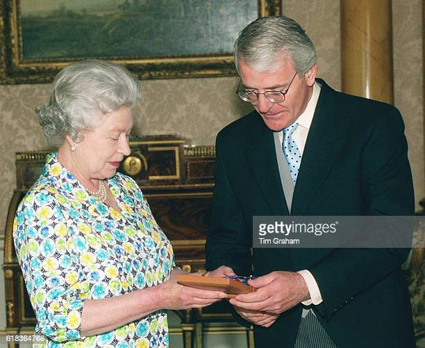 Queen Elizabeth II in diplomatic meeting with her Prime Minister awards John Major with an honour