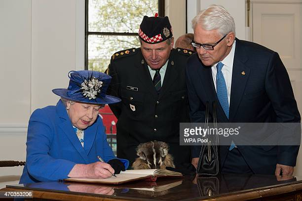 Queen Elizabeth II in her role as ColonelinChief of the Calgary Highlanders regiment signs the visitors book ahead of a reception at Canada House at...