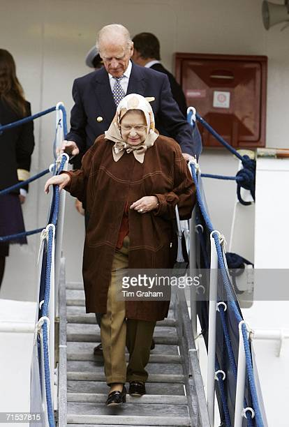 Queen Elizabeth II in suede coat headscarf and trousers with Prince Philip Duke of Edinburgh leave the Hebridean Princess at Stornoway after a...