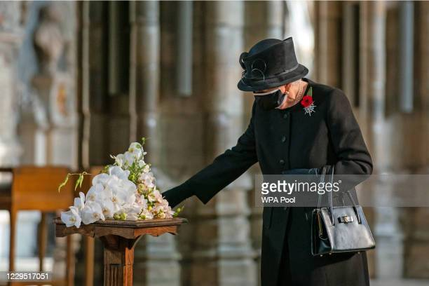 Queen Elizabeth II inspects a bouquet of flowers placed on her behalf at the grave of the Unknown Warrior by her Equerry, Lieutenant Colonel Nana...