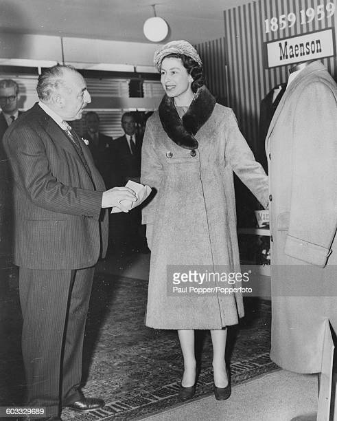 Queen Elizabeth II inspects clothing on the Joseph May and Sons Ltd stand during a tour of the Textile Show at Earls Court exhibition centre in...