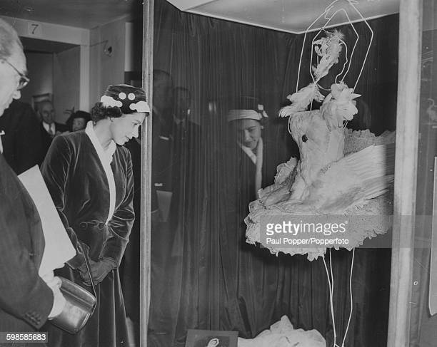 Queen Elizabeth II inspects the dress worn by Anna Pavlova made from swan feathers for her performance of 'Swan Lake' during a visit to the Pavolva...