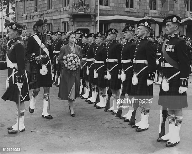 Queen Elizabeth II inspects the Guard of Honour of the Argyll and Sutherland Highlanders outside Ballater railway station Ballater whilst holidaying...