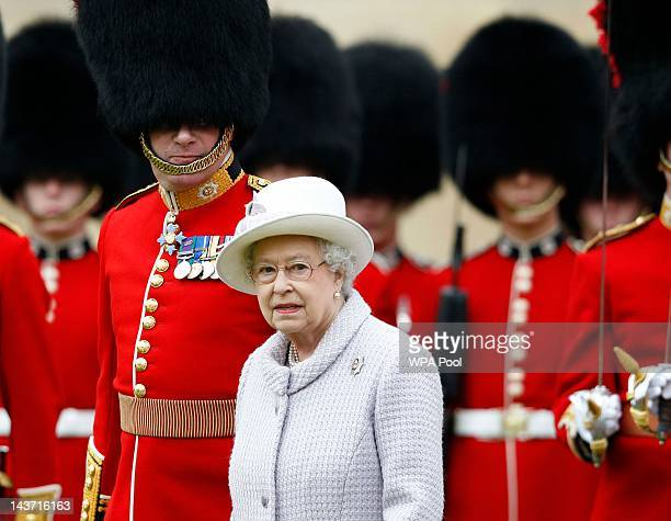 Queen Elizabeth II inspects the guards during a ceremony to present new colours to the 1st Battalion and No. 7 Company the Coldstream Guards at...